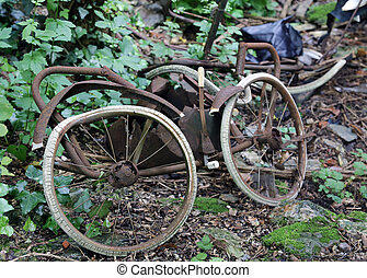 rusty old stroller for newborns abandoned in the forest