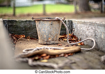 Rusty old vintage iron bucket in a wooden handcar with brown autumn leaves and a used piece of rope.