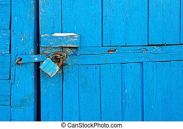 Rusty padlock on old wooden door