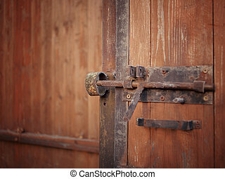 rusty padlock on wooden door - Shallow depth of field image...