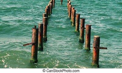 Rusty poles in the sea