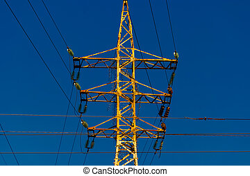 Rusty power- tower against deep blue sky