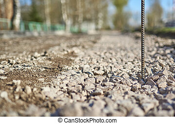 Horizontal shot of rusty reinforcement rod against the background of a road being repaired in a blur.