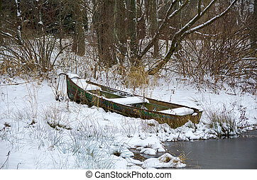 rusty row boat in snow - Abandoned row boat in snow by rural...