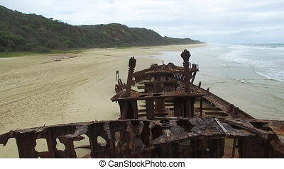 Rusty ship on beach - An aerial shot of a rusty destroyed...