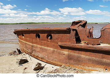 rusty ship on the shore of river