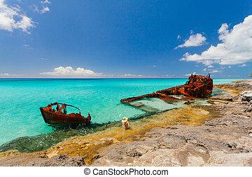 Rusty ship wreckage on a peaceful beach in the Bahamas