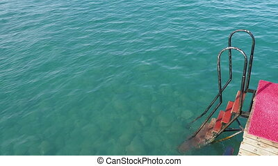 Rusty stairs from pontoon into water. Mediterranean sea....