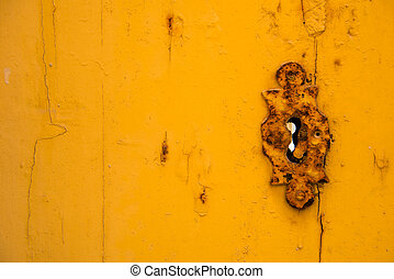 Rusty vintage keyhole on a yellow door