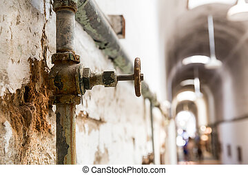 Rusty water pipes of old prison. Blur hallway on background,