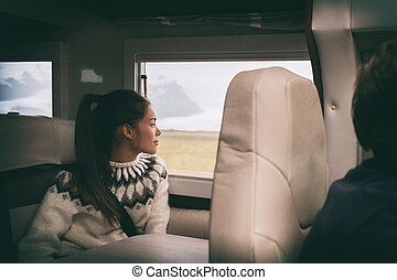 RV camper van travel Asian girl sitting in back of motorhome car on Iceland road trip. Europe vacation lifestyle.