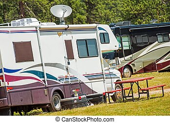 RV Motorhomes Camping. Recreation Vehicles on the Campground. Class C and Class A Diesel Motorhome in the Background.