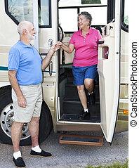 RV Seniors - Chivalry - Polite senior man helps his wife...