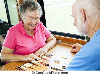 RV Seniors Play Board Game - Senior couple in the kitchen of...
