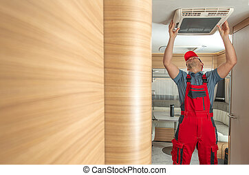 RV Service Worker Replacing or Fixing Travel Trailer Air Condition