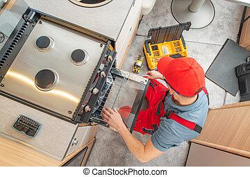 RV Technician Replacing Broken Travel Trailer Gas Stove
