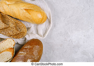 Rye bread, a wheat loaf, and a baguette with sesame seeds lying on a white towel on lite grey textured background.