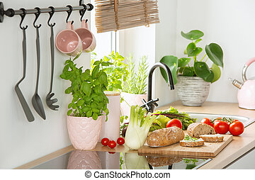 Rye bread on a cutting board, tomatoes and vegetables on a white kitchen interior countertop with Basil herbs in a pink pot