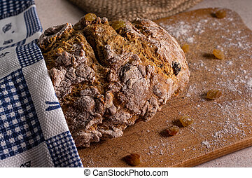 Rye bread on the cutting board covered with towel