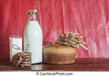 Rye bread with full bottle of milk on wooden table.