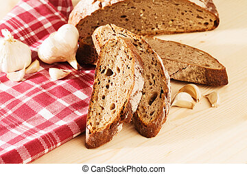 rye bread with garlic and a towel on wooden background