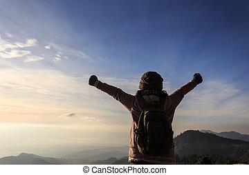 ryggsäck kvinna, stående, på topp om, a, fjäll, med, uppresta händer