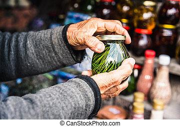 rynkig, gammal, kvinna lämnar, hålla, kruka, med, hemlagat, marmelad, från, barrträds-, bladen