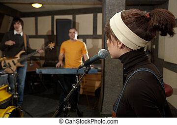 sänger, m�dchen, bei, microphone., fokus, auf, kopf, microphone., elektro, gitarre spieler, und, keyboarder, in, fokus