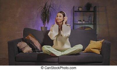 séance, écoute, sans fil, headphones., girl, confortable, jeune, happy., sofa, femme, salle, musique