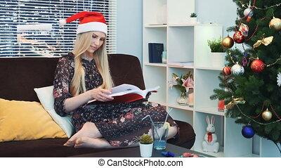 séance femme, chapeau, haut, milieu, livre, santa, fin, maison, lecture, attentivement, intelligent, sofa