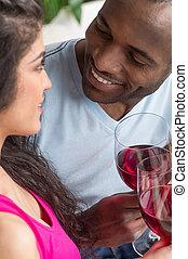 séance femme, couple, ensemble, leur, américain, thirties., boire, homme, africaine, vin., sourire heureux, rouges, lunettes