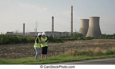 séduisant, ingénieur, femmes, discuter, et, évaluer, usine, travail, procédures, utilisation, pc tablette, près, pétrochimique, raffinerie