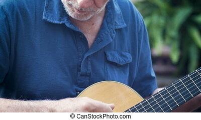 séduisant, sain, vieillissement, homme aîné, jouer, guitare acoustique, inclinez