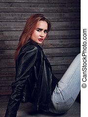sério, cabelo vermelho, assento mulher, em, revestimento preto, azul, calças brim, ligado, rua, parede, fundo