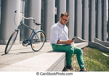sério, homem jovem, em, fones, trabalhar, laptop, enquanto, sentando, em, ao ar livre, de, escritório