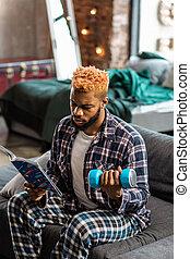 sério, homem jovem, sendo, envolvido, em, leitura