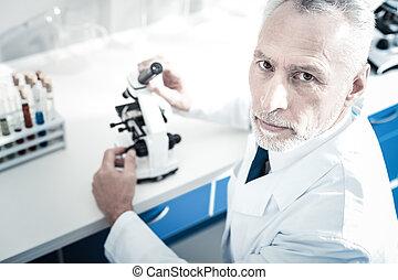 sério, microscópio, homem, segurando, bonito
