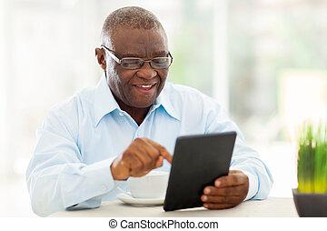 sênior, homem americano africano, usando, tabuleta, computador, casa