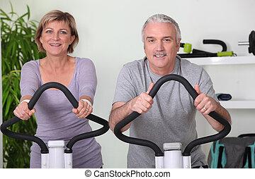 sênior, montando, par, bicicletas, ginásio