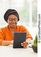 sênior, mulher africana, usando, tabuleta, computador