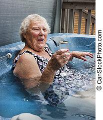 sênior, senhora, relaxante, em, um, banheira quente, com, champanhe