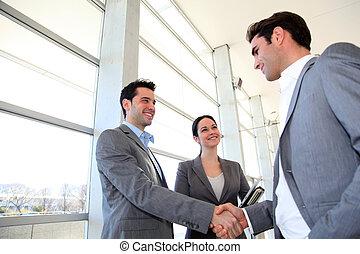 sócios, reunião negócio, mãos sacudindo, corredor