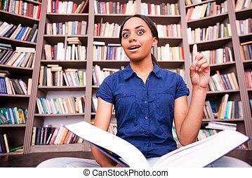 sólo, inspired., sorprendido, hembra africana, estudiante, sujetar un libro, y, señalar con el dedo arriba, mientras, sentado sobre el piso, en, biblioteca