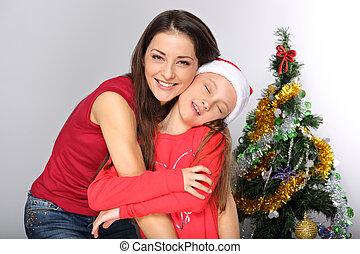 söt, ögon, pälsfodra, dotter, jultomten, henne, sats, grönt träd, naturlig, bakgrund., krama, stängd, mor, studio, le, avnjut, hatt, jul, lycklig