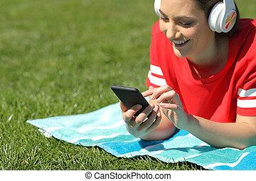 słucha, zadowolenie, telefon, muzyka, czytanie dla przyjemności, dziewczyna, trawa, szczęśliwy