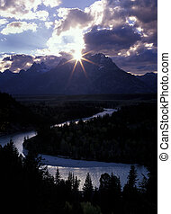 sun peaks out into a star burst between clouds and The Grand Teton, with the Snake River forming an s-curve in the foreground