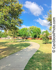 S-curved pathway with mature oak trees at residential park and suburban houses in Texas, USA