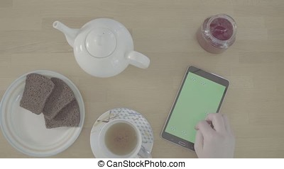 S-log. Green screen. Female hands scrolling a tablet -...