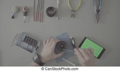 S-log. Male hands repair lens on grey table - S-log. Top...