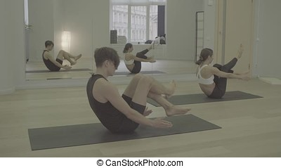 S-log. Yoga class. People doing yoga asanas in bright...